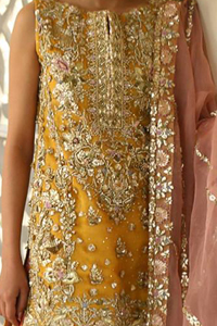 Amber shirt adorned with mainly light golden embellishment on neckline, hemline and side slits. Pink peach dupatta adorned with embellished border and stripes. Multiple color sharara adorned with border on hemline, stripes and motifs.