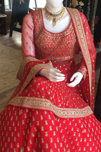 Simple but elegant deep red bridal blouse having dull golden and light antique embellishment. Appliqued with bright red fabric. Red lehengha having large borders of hand embellishment and small motifs spray above the hemline. Same border as on lehengha has been implemented on dupatta with motifs spray all over it.