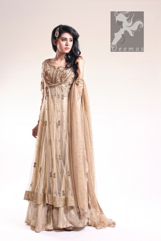 Fawn Blouse adorned with antique gold and brown embellishment. Fawn pure crinkle chiffon gown center slits border has been adorned with light embellishment border and follows small motifs and sequins spray all over it. Pure crinkle chiffon sharara and dupatta has sequins spray all over it.