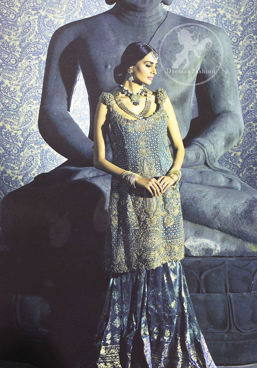 Bluish Slate Grey heavily embellished shirt is decorated with dull golden, champagne and antique shades of embroidery. The shoulders is embedded with beautiful antique 3D floral work. Skirt having embellished border on the hemline. The velvety lehengha is adorned with block print floral pattern all over and border on edges.
