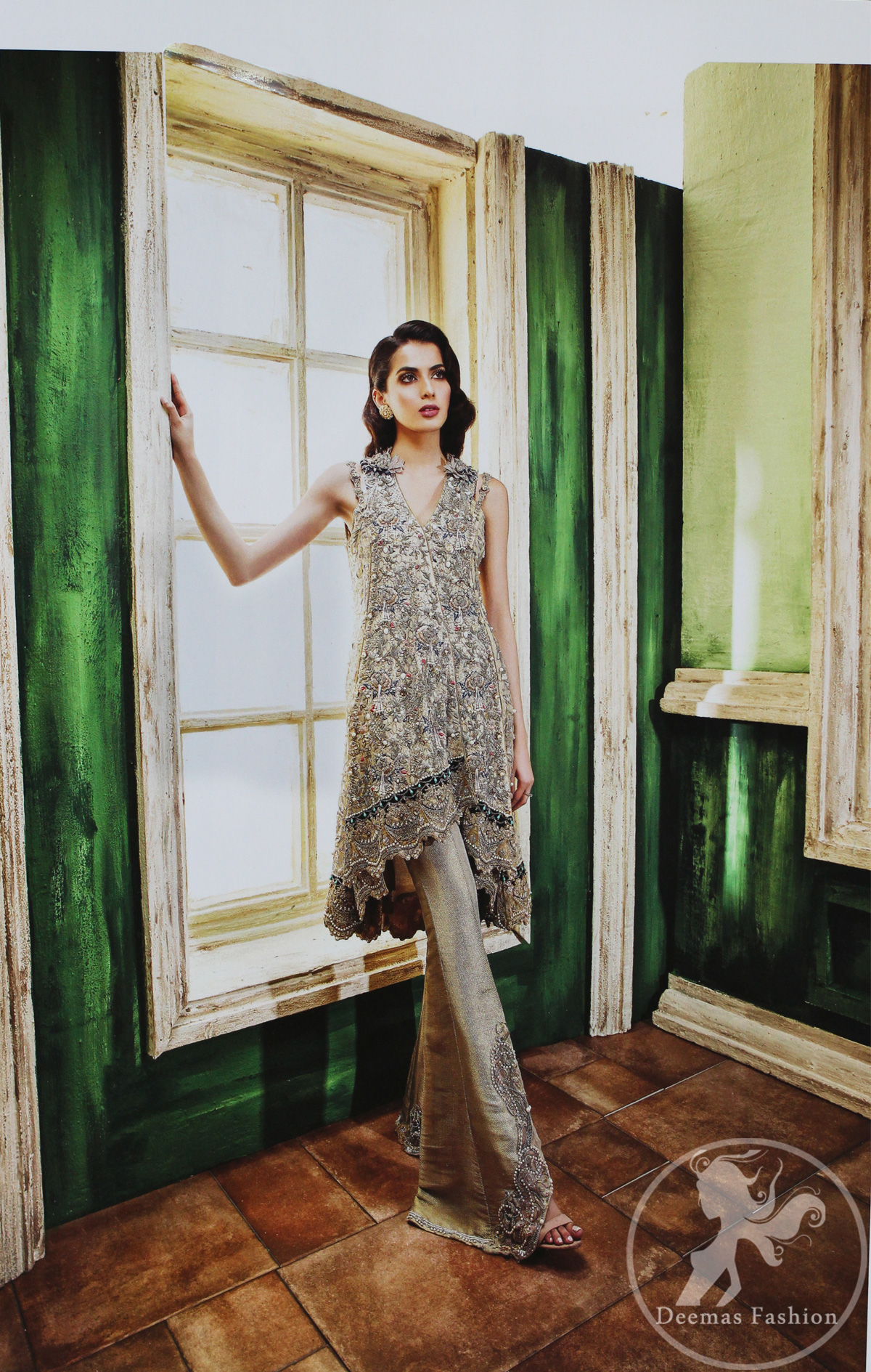 Grey olive floral embroidered high and low front open short frock. Frock is finessed with kora, dabka, pearls, sequins and swarovsky. The daman of the frock is beautifully enhanced with scalloped border and silhouettes. This shirt is adorned with 3D floral embroidered motifs having V shaped neckline. Top is coordinated with pajama having embroidered motifs.