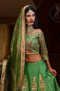 This outfit is embellished with gotta lace. It is meticulously highlighted with kora dabka, tilla, sequins and pearls. Sleeves are adorned with gotta lace in criss cross pattern. Boat-shaped neckline ornamented with floral motifs. It comes with hippie green lehenga adorned with floral embroidery. It is coordinated with chiffon dupatta embellished with applique and sprinkled sequins all over.