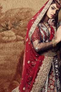 Black floor length net paneled gown is beautifully embellished with silver kora dabka, tilla, pearls and sprinkled sequins all over. It comprises with maroon blouse and skirt. The skirt is ornamented with floral motifs done with silver gold kora dabka, tilla, kundan and sequins work. This outfit is coordinated with maroon dupatta with embroidered borders on all four sides and sequins work on the ground.
