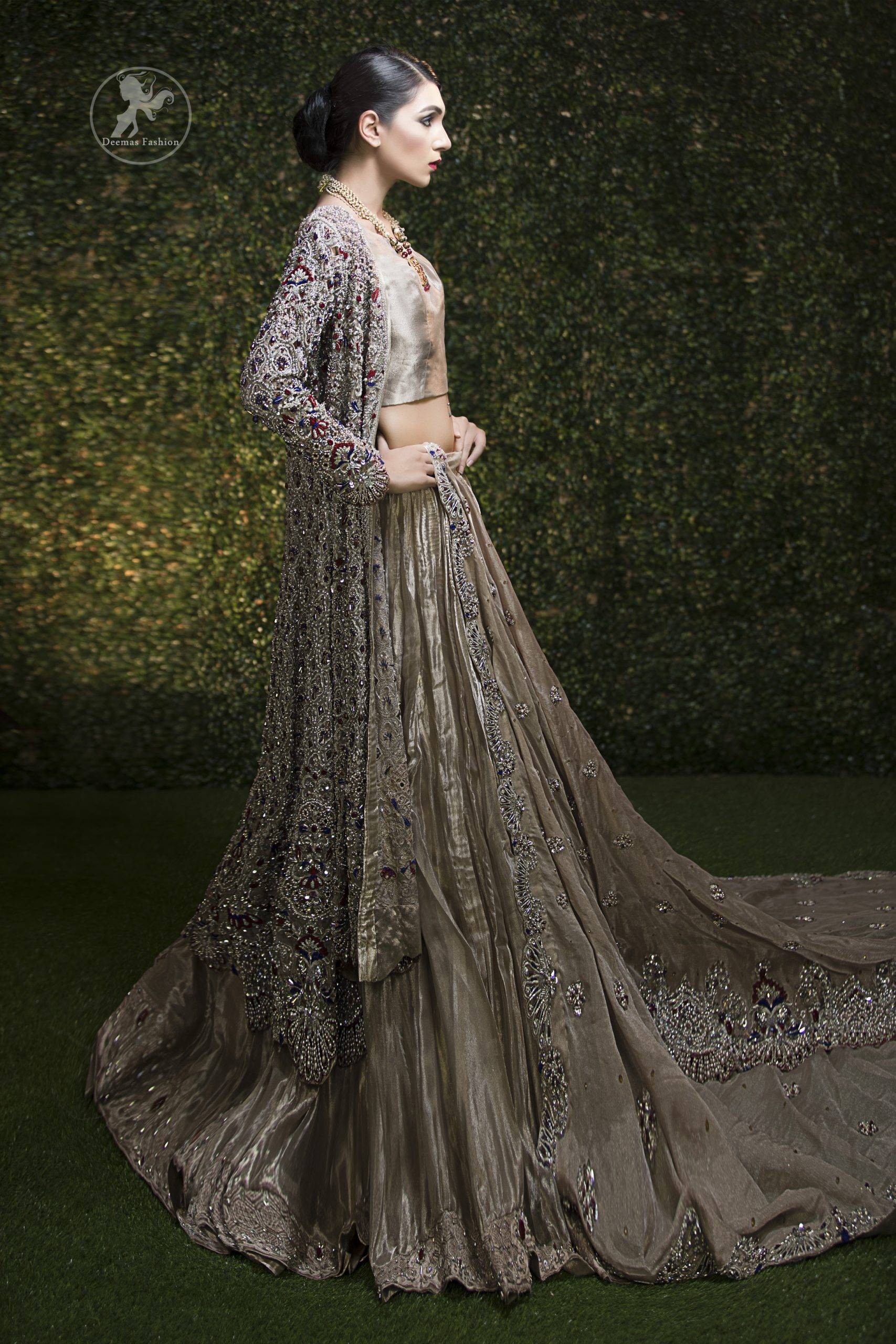 This bridal dress is beautifully decorated with floral embroidery. Gown is allured with floral embroidery and embellished scalloped border. It is adorned with kora, dabka, tilla, sequins, stones and pearls. It comes with an exquisite lehengha with embroidered border to give it a regal look. Dupatta comprises of floral thread embroidery allured with embellished border and floral motifs all over it.