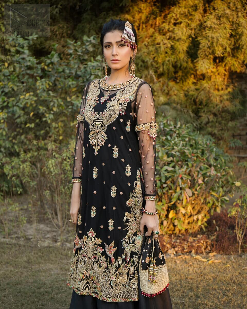 This elegant ensemble turns timeless piece into a chic fantasy. Steal the show with this endearing chiffon outfit with intricate yet rich embroidery. Artfully crafted neckline with detailed golden zardozi work. The hemline is ornamented with a central large motif and adorned with jaal. Furthermore, side slits are also decorated with floral embroidery and floral motifs are decorated with multiple color thread embroidery. The back is perfectly loaded with zardozi work. This outfit is comprises with black sharara and chiffon dupatta having sequins spray all over.