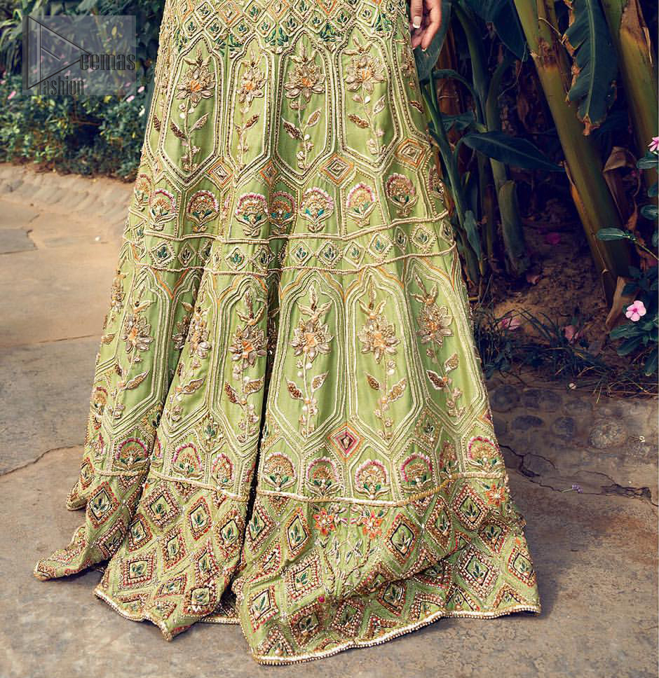 Nothing speaks of femininity and class louder than this mehndi outfits for bridesmaids. Steal the moment with this outfit with this shabby chic statement intensified with rich thread embroidery all over the front and bold patterns at daaman od the lehenga. Furthermore, it is enhanced with floral motifs all over decorated with multiple color thread embroidery. It is coordinated with parrot green blouse done with golden zardozi work and three quarter sleeves. Style it up with chiffon dupatta scattered with sequins all over.