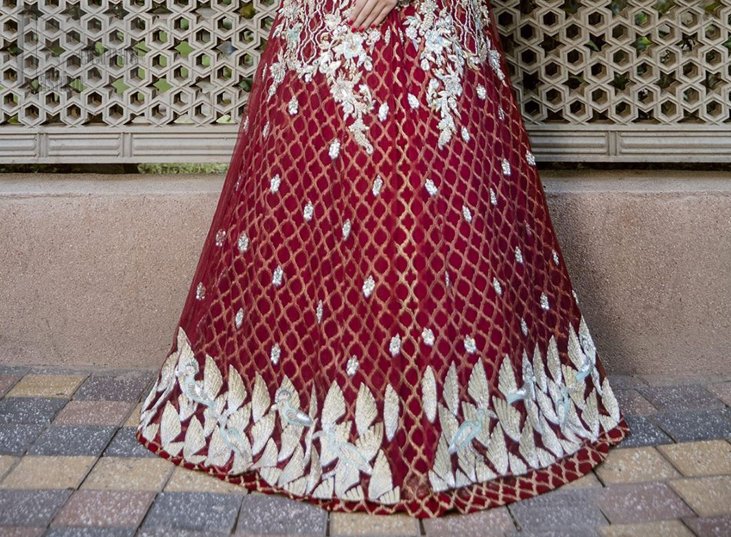 This front open marron maxi is creating a dreamy composition. The chic yet elegant front open maxi is decorated with floral embroidery , heavily embellished bodice and floral bunches. Hemline is even more enhanced with birds motifs finished with jamawar lining adorned with geometric patterns in it. The embroidery is done with silver and white kora, dabka, tilla, and pearls. It comes with straight trousers allured with sprinkled motifs on dupatta dupatta finished with silver lace all around the edges.