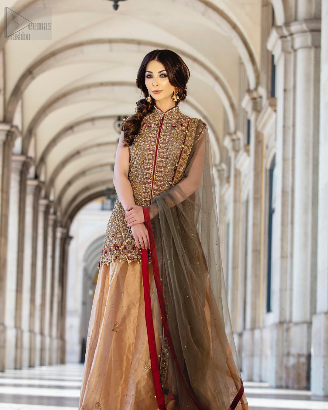 Our selection of wedding dresses offers simple evening glamour dresses. Add a taupe gray color to your wardrobe with our modern styled front open shirt enhanced with embellished geometric patterns. The neckline is beautifully designed with collar neck and scalloped hemline is emphasized with dangling pearls and multiple color embroidery. It is paired with taupe gray dupatta with one sided hand embellished border and sprinkled sequins all over. Compliment the look with fawn lehenga adorned with floral bunches. The combination of fawn and taupe gray is absolutely breathetaking.