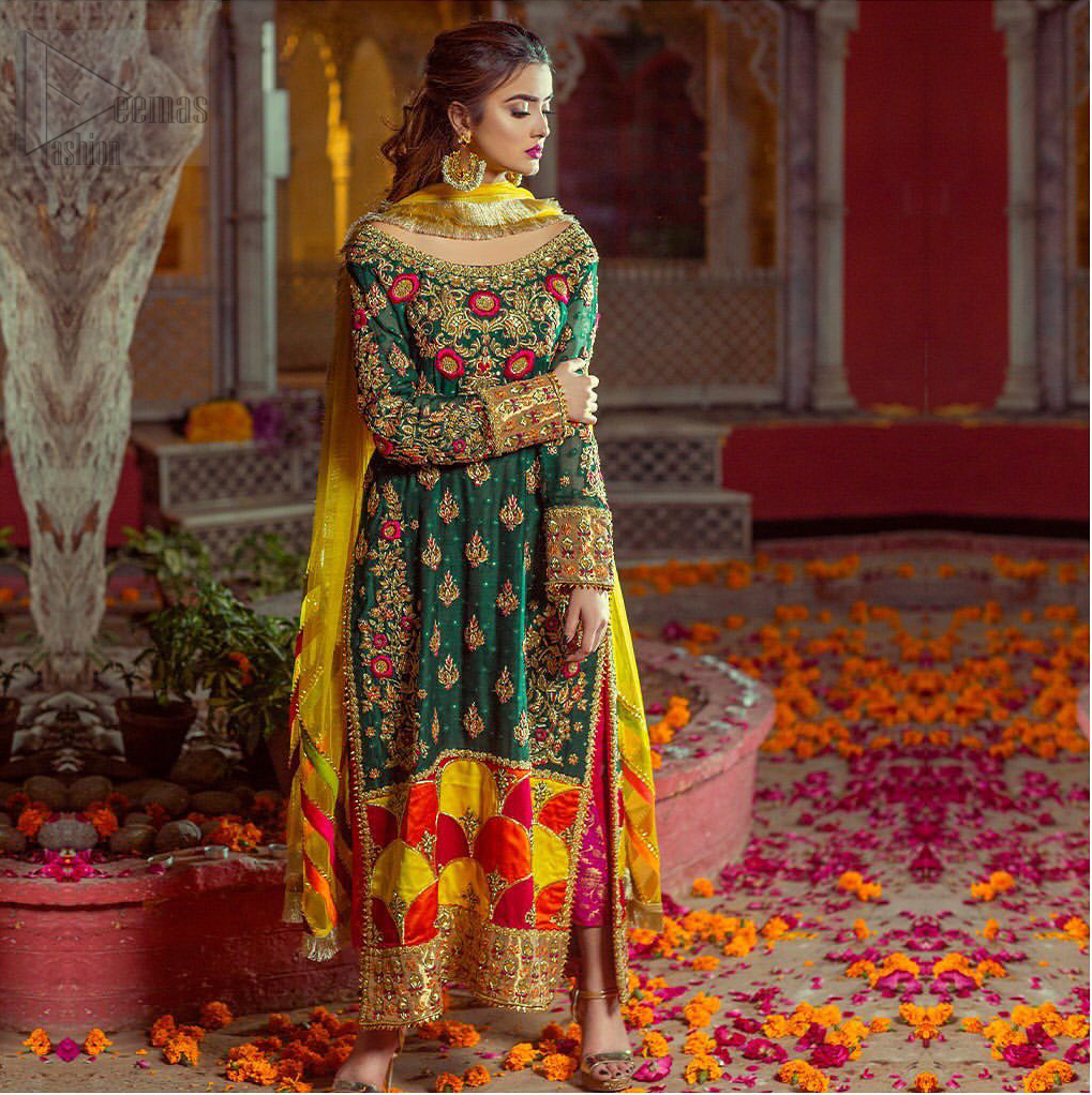 Beautifully elegant with a modern twist. This beautiful outfit comes with bottle green long shirt and colorful applique hemline, making an elegant, traditional and stylish mehndi dress. Excellence of craftsmanship is evident with intricate geometrical detailing that features the use of kora, dabka, crystals, sequins and glass beading. Furthermore it is enhanced with colorful floral motifs and golden zardozi work. It comprises with pink capri pants. Elegance is personified when it gets paired up with net dupatta with kiran on all sides and colorful strips on pallu.