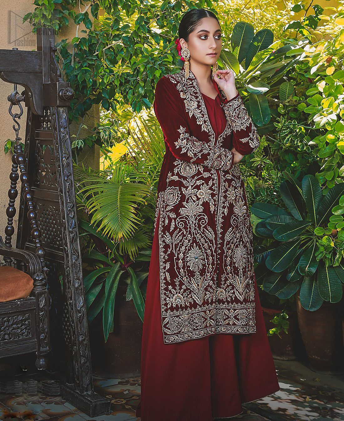 Steal the show with this endearing velvet outfit with intricate yet rich embroidery. The chic yet elegant front open shirt is decorated with embroidered patterns, embellished collar neckline and floral bunches. Hemline is even more enhanced with detailed zardozi work. The back of the shirt has a central large motif on the bodice while the zardozi work creates drama on both front and back panels. Beautifully paired up with maroon palazzo pants. Finish the look with maroon organza dupatta adorned with tiny floral motifs all over.