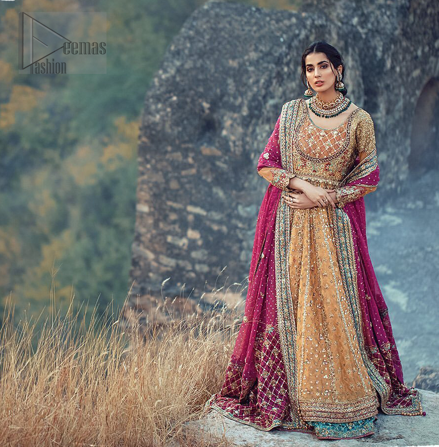 This exceptionally detailed anarkali frock is cut in a seductive fit and flare silhouette that's sure to turn heads. The bodice with round neckline is adorned in richly beaded work with fabulous sparkle and zardozi work. Furthermore the panels of the shirt is vertically adorned with golden kora, dabka, tilla work and various flora motifs meticulously using on the ground. The frock is comprises with ferozi lehenga emphasized with criss cross patterns done with golden embellishment. Elegance is personified when it gets paired up with an embroidered dupatta with alternating motifs and sequins detailing.