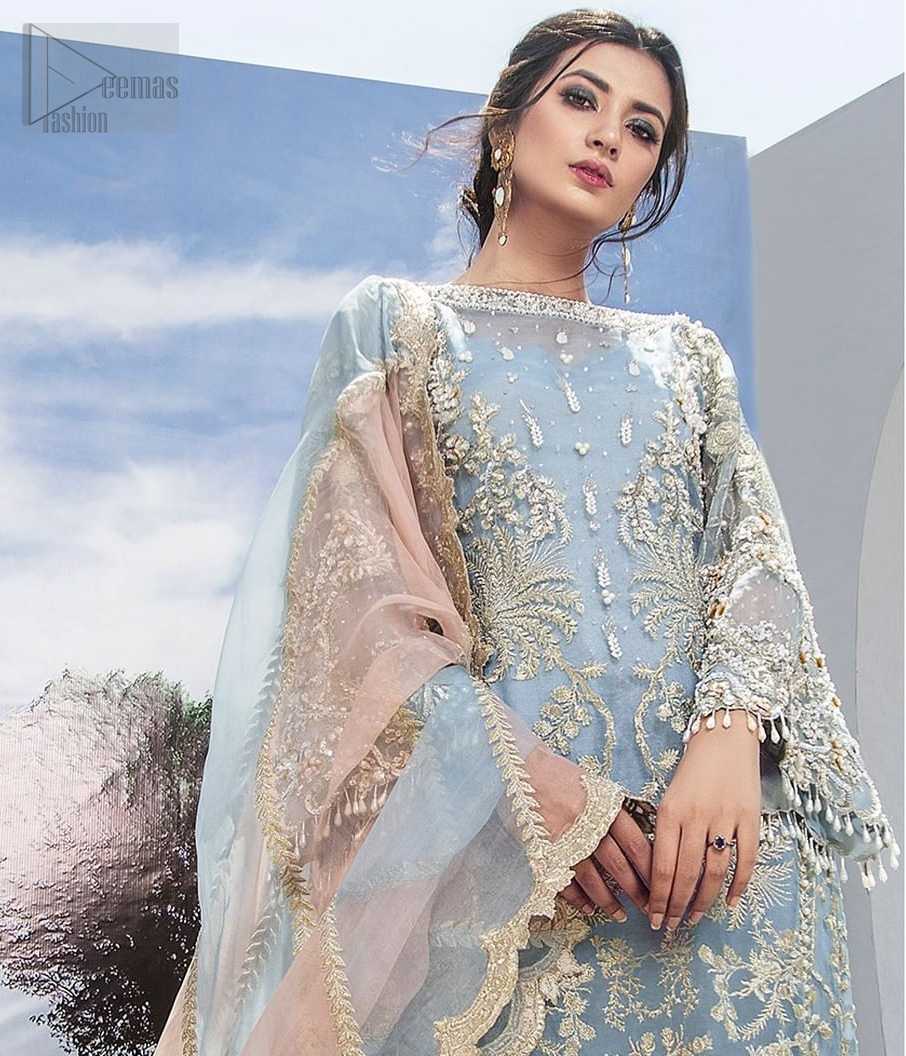 Intricate details, flamboyant silhouettes and mastery of colour are what makes this dress stand out from the rest. This is one of the elegant pieces are sure to stay in your heart and your wardrobe forever. The front of the shirt is beautifully ornamented with floral motifs and bootis, also a delicate arrangement of geometric patterns on the hemline with light golden and silver zardozi work. The back of the shirt is accentuated with a large central motif and scattered tiny floral motifs all over. It comprises with ferozi capri pants emphasized with bottom. To complete the look, go with a gradient dupatta having geometric patterns on pallu and scalloped border along the length. Furthermore the outfit is fully decorated with scalloped finishing and tassels.