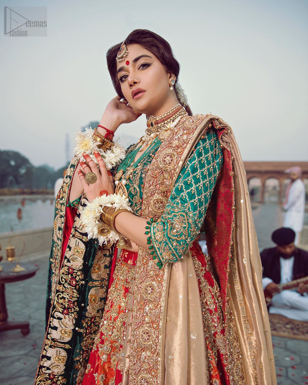 Classic, timeless and truly beautiful, our bridal dress is perfect for your unforgettable day. Excellence of craftsmanship is evident with intricate detailing that features the use of zardozi work. The blouse is beautifully adorned with geometric patterns and floral embroidery with golden zardozi work and finished with dangling beads. Complete the look with artfully coordinated lehenga which is ornamented with a bold and captivating design with a traditional intricate embroidery and scattered tiny floral motifs. The combination of red and orange for lehenga is also captivating. Elegance is personified when it gets paired up with golden dupatta having four sided embroidered border.