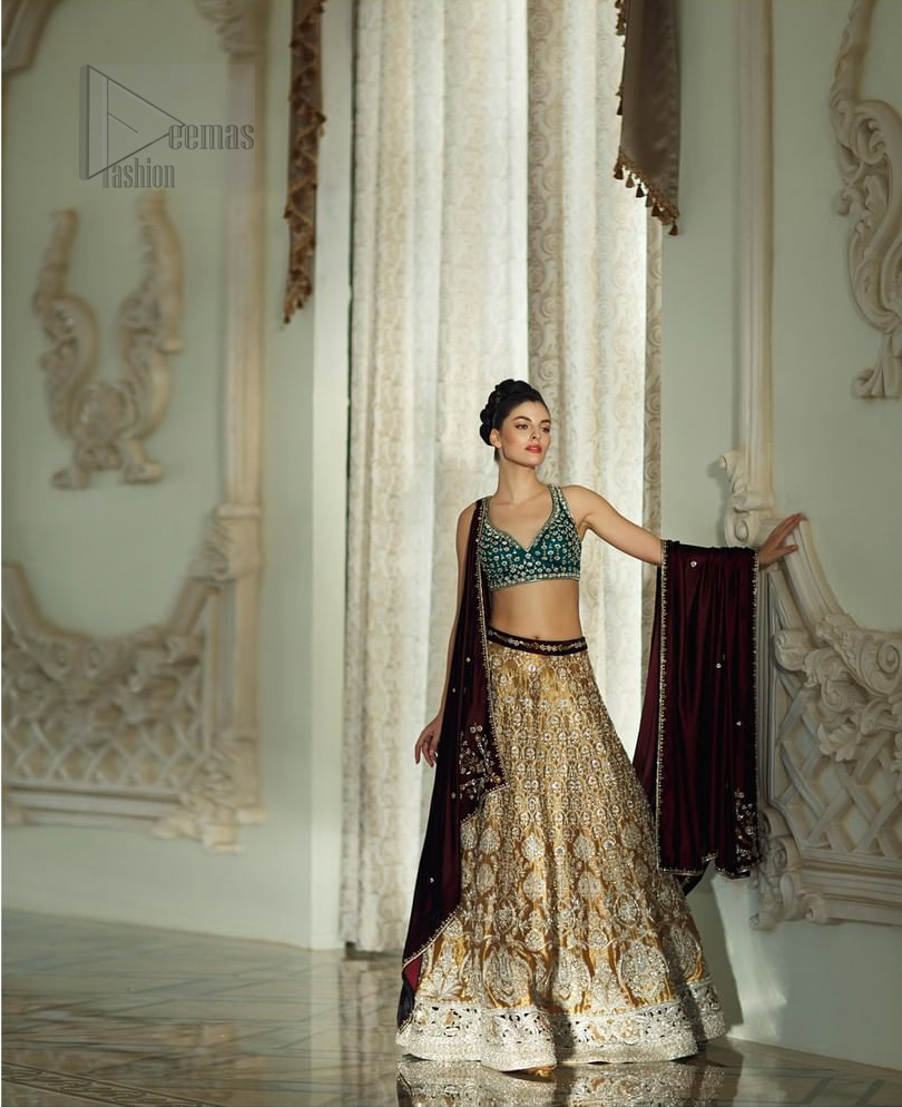 Delicately crafted and personifying chic elegance with an element of grandiose. Gussy up in this luxuriously designed lehenga blouse emboldened with intricate embroidery along with beautiful rich patterns and delicate details at the bottom. The maroon waist belt on lehenga make it so classy. It comprises with teel blouse adorned with tiny floral motifs in the shade of silver. The outfit is pair up with maroon velvet dupatta emphasized with silver and golden zardozi work on all four sides.