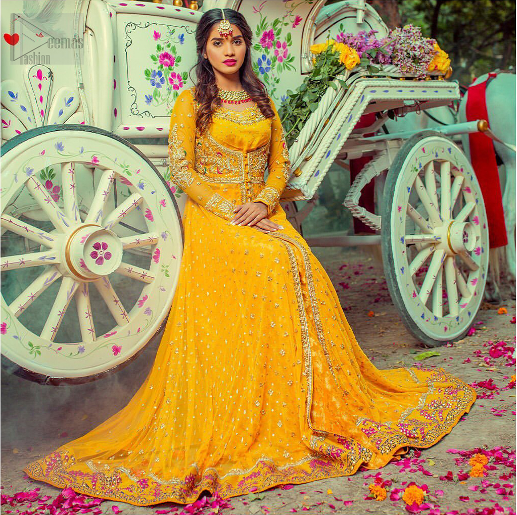 Adorn yourself with this breath-taking mehndi outfit. Be it the next mehndi right after a family festivity. A delicate arrangement of hand embellished tiny floral motifs on the ground and heavily embellished from bodice and neckline with golden and pink zardozi work. The daaman is emphasized with intricate zardozi details and multiple color thread work that gives perfect ending to this outfit. Pair it up with yellow churidar pajama. To complete the look, go with yellow chiffon dupatta scattered with tiny floral motifs and kiran on all four sides.