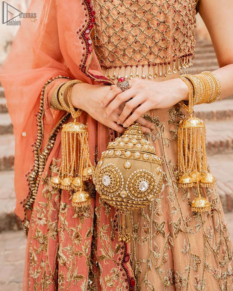 Crafted with love. This beautiful bride is a vision of impeccable grace and elegance in a divinely crafted bridal couture, with the exquisite embroideries that add the royal touch to the outfit. This off-shoulder blouse is meticulously crafted with zardozi work in the shades of golden and antique, finished the blouse with dangling tassels. The lehenga is emphasized with hand embellished floral embroidery with kora, dabka, tilla, sequins and beads all over. The look is complete when it gets paired up with an organza dupatta having scalloped finishing along the length and floral jaal on both sides of pallu.